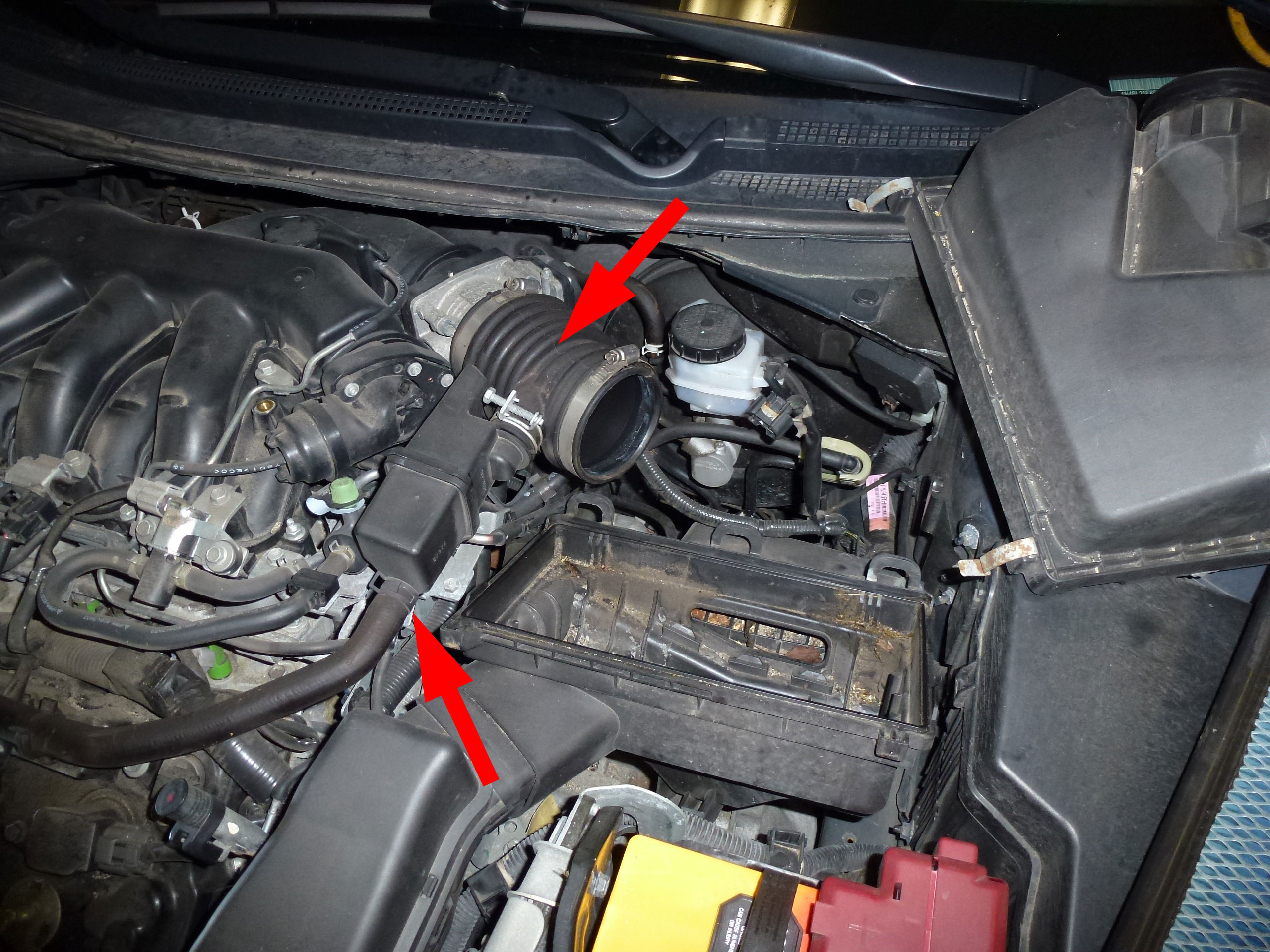 Lift the cover out of the way. Disconnect the vacuum line on the bottom of the air intake assembly and remove the intake hose.