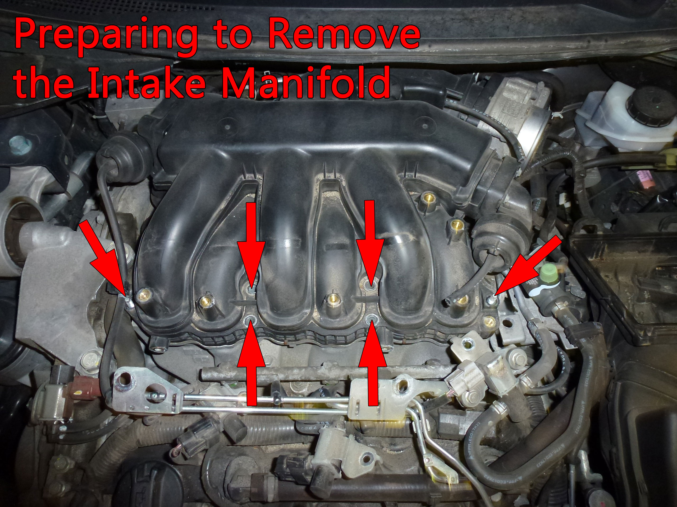 Remove the bolts and nuts that attach the upper manifold to the lower manifold. The outer two fasteners are nuts and the other four are bolts. At this point, there are a few more steps before the manifold can be removed.