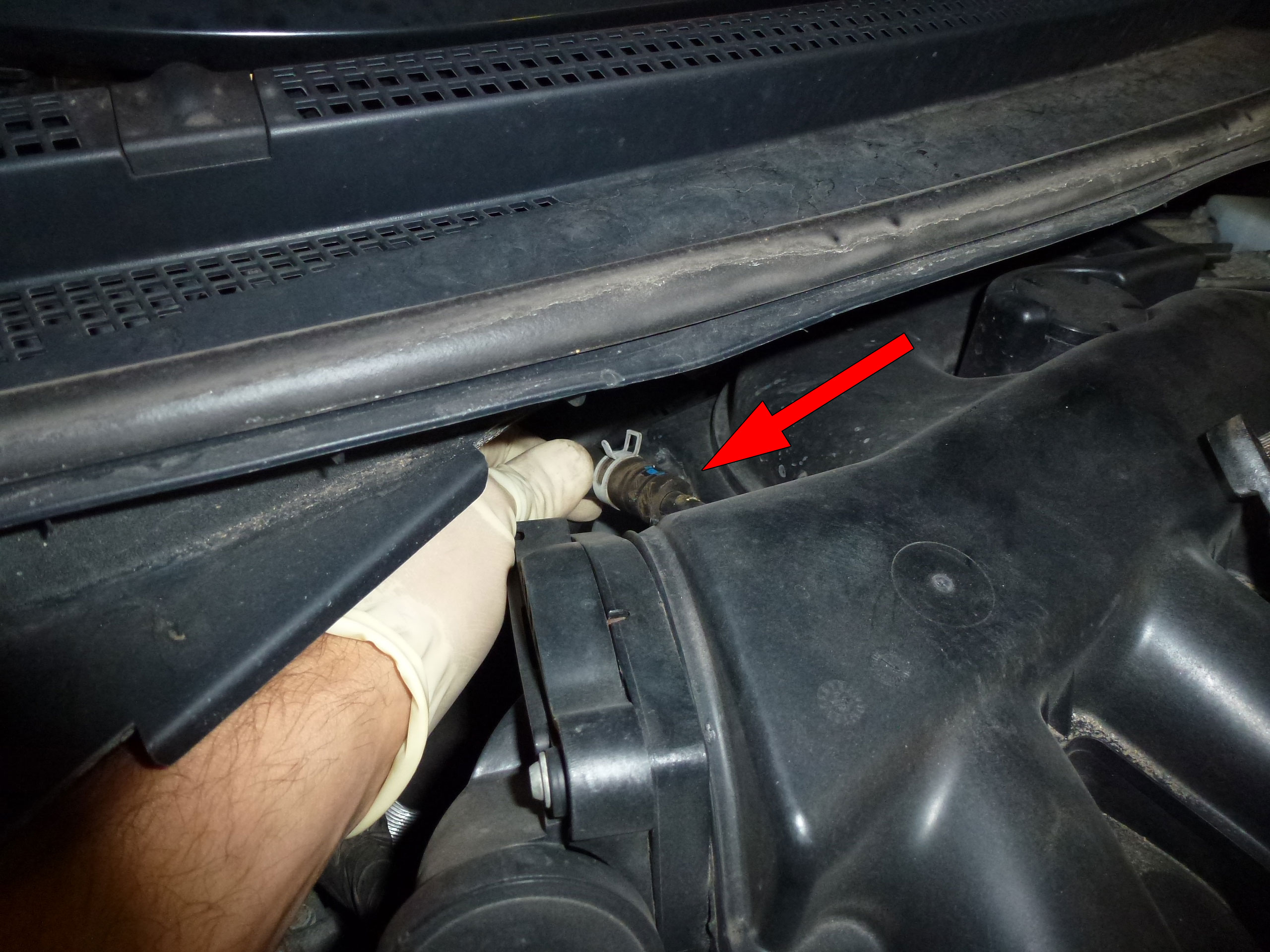 Remove the vacuum line from the back of the manifold by moving the clamp and twisting with pliers before removing.