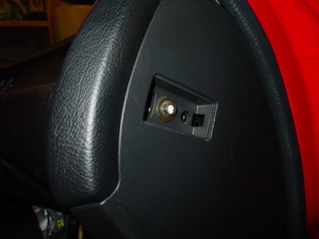 There is a plastic cover on each side of the dash. Pop them out to gain access to the screws behind them. Remove the screws and set them aside.