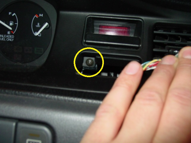 Pop the hazard button by prying it out with a screwdriver. Under the button is a screw that needs to be removed. There are two more screws that need to be removed just above the instrument cluster.