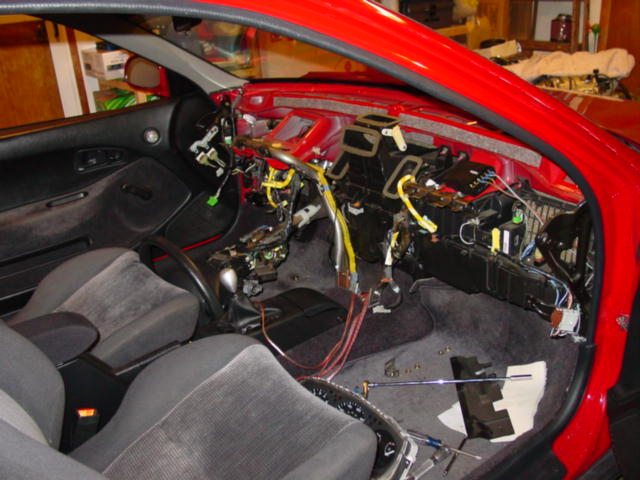 At this point, the dash can come out.  The dashboard harness plugs into the chassis harness just above the fuse panel.  As you pull it away, take care to disconnect the ground wire that attaches to a metal tab behind the cluster. Watch or any other connectors you have missed.