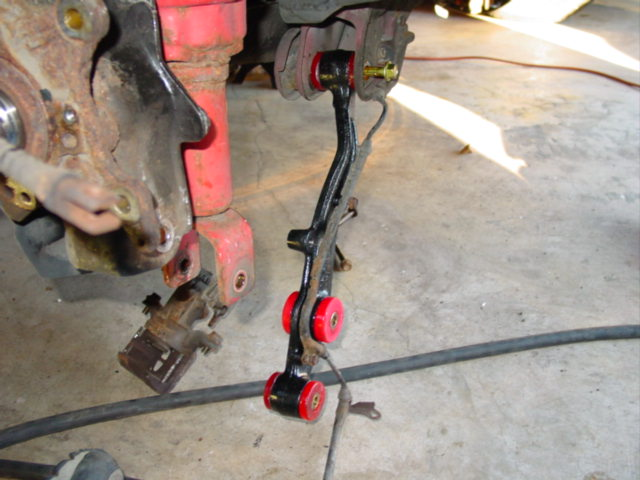 The new control arms, with sway bar mounts, are loaded with new bushings and ready for installation.